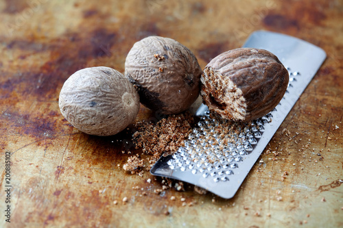Fototapeta Making nutmeg powder process. Nuts silver grater. Kitchen still life photo. Shallow depth of field, aged brown rusty background. Selective focus. obraz