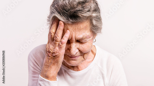 Tuinposter Klaar gerecht Studio portrait of a senior woman in pain. Close up.