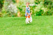 canvas print picture - Dog with ball in mouth runs from kid playing chase game at summer lawn