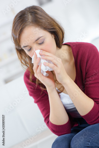 ill young woman is sneezing in a tissue Wallpaper Mural
