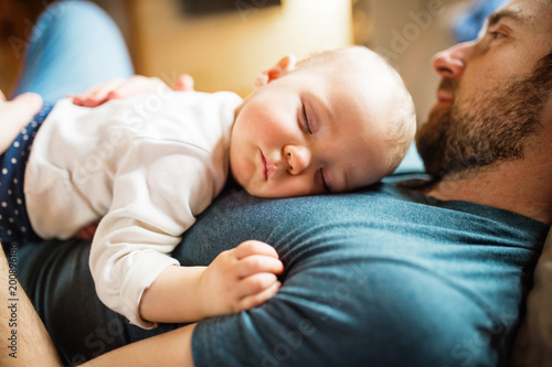 Obraz Father with a baby girl at home sleeping. - fototapety do salonu
