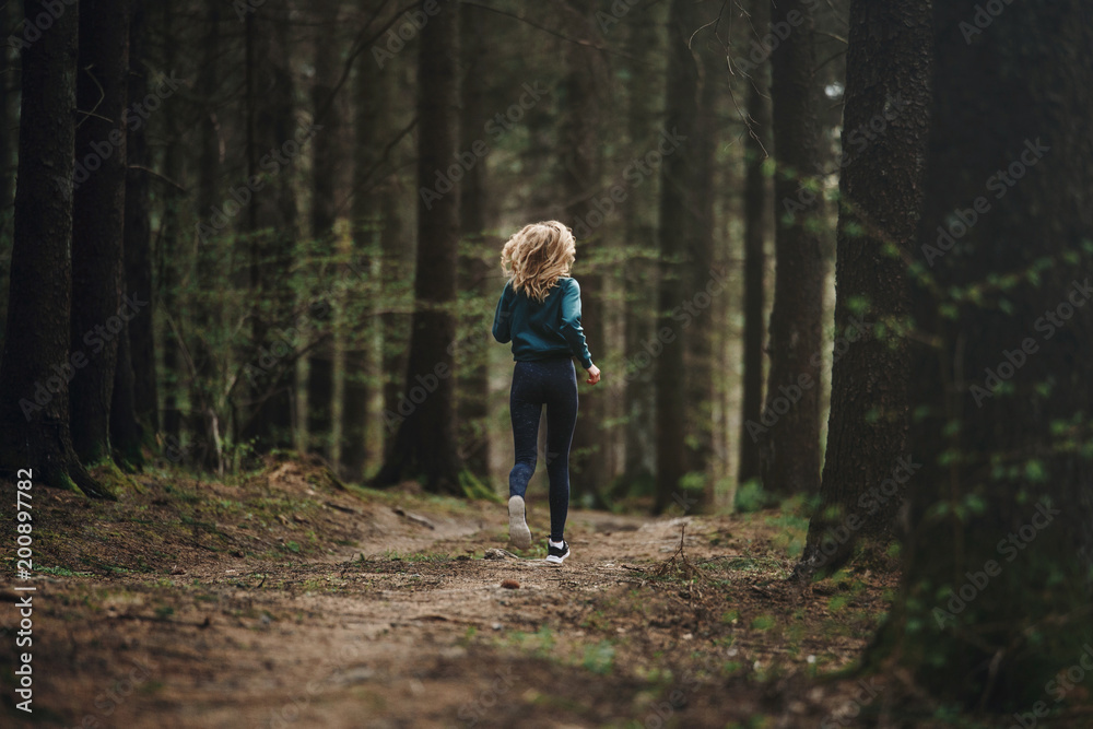 Fototapeta Young fitness woman running in the forest trail