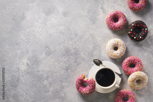 Sone pink and white donuts with cup of coffee over grey stone texture