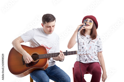 Photo  Musical artists sing and play acoustic guitar.