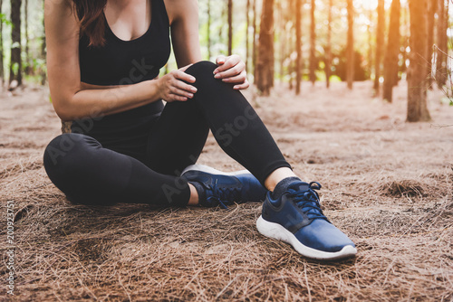Fotografiet  Girl has sport accident injury in forest at outdoors
