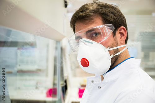 Man in safety mask and goggles looking at camera while working ininnovative lab.