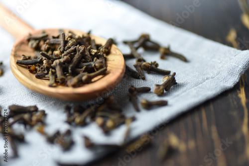 Fototapeta Cloves on a wooden spoon, old wooden background, selective focus