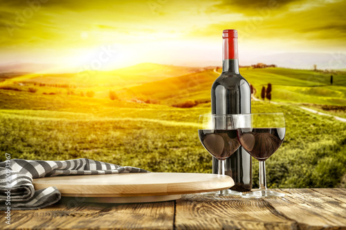 Fotografiet  Wine on desk and Tuscany landscape