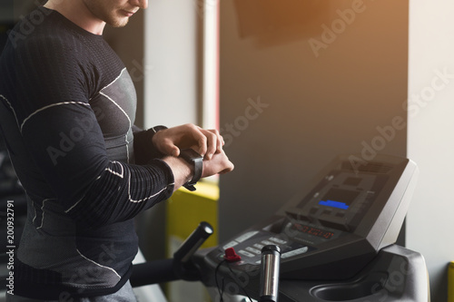 unrecognizable man using fitness tracker in gym buy this stock