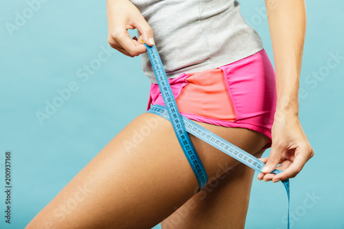 Fotografia  Fitness woman measuring her thigh on blue