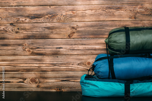 Poster Camping camping equipment, sleeping bags, tent s on wooden background with copy space for text