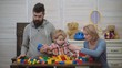 Young family in playroom. Love family concept. Mom, dad and boy with toys build out of plastic blocks. Parents and son smiling, make brick constructions.