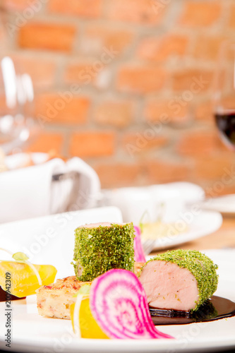 Poster Dairy products Roast pork tenderloin with crispy potato bread, marinated beetroots and green pepper sauce served in a restaurant