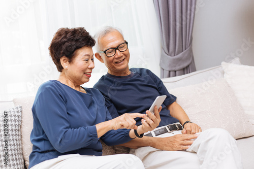 Fotografía Senior Asian couple grandparents using a smart phone together on sofa at home