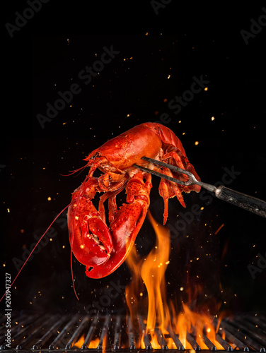 Fotobehang Schaaldieren Flying whole lobster from grill grid, isolated on black background