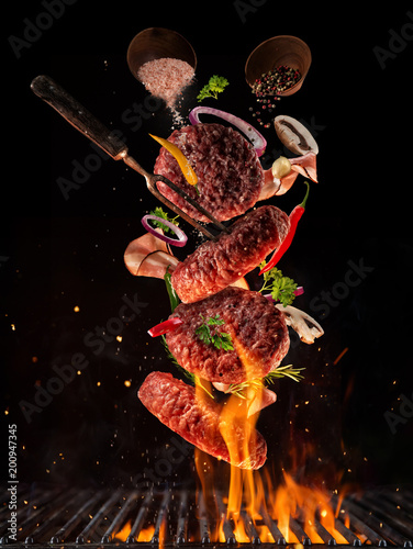 Foto op Canvas Mediterraans Europa Flying pieces of beef meat pieces on hamburger from grill