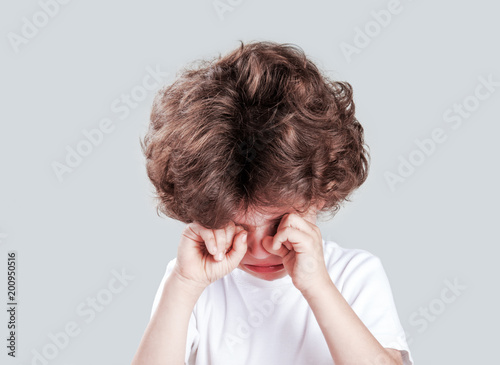 Cute little curly-headed boy in a white t-shirt is crying and looking at the camera Fototapeta