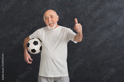 Senior man with soccer ball showing thumb up