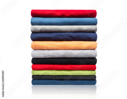 Fotografía  New colored clothing stacked in a pile close-up on white background