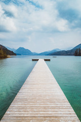 Fototapeta Vintage Wooden landing stage at alpine lake in summer