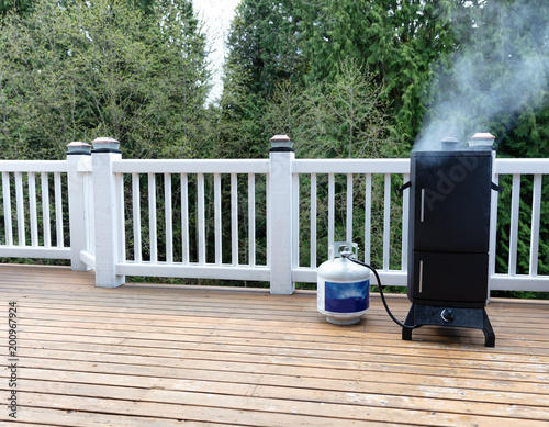 Smoker with fresh smoke coming out of BBQ cooker on outdoor deck of home