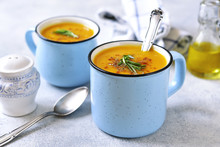 Two Portions Of Pumpkin Creamy Soup In A Blue Emamel Mugs.