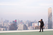 Business man stand on rooftop city while talking mobile phone