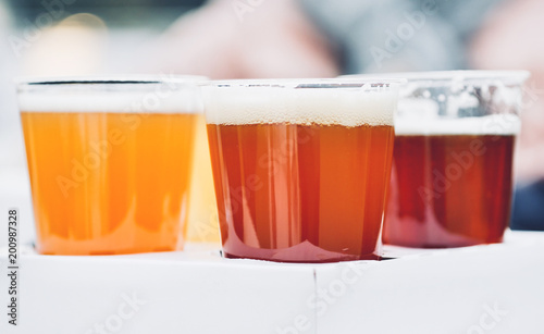 Платно three glasses of craft beer, pale, wheat and ipa, beer flight for tester