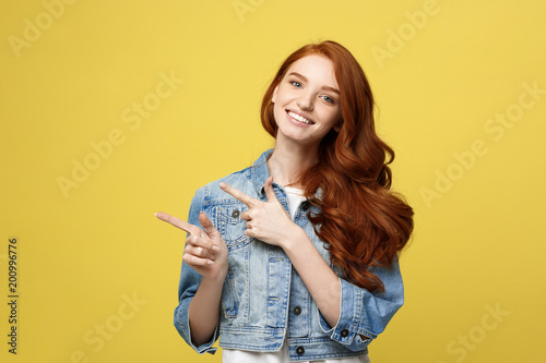 Fototapeta Lifestyle Concept: Happy excited cuacaisan tourist girl pointing finger on copy space isolated on golden yellow background obraz na płótnie