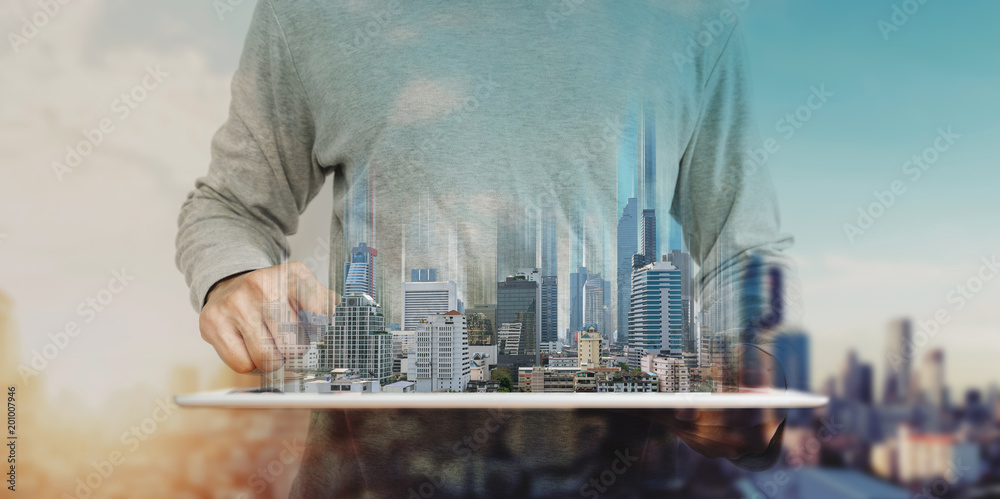 Fototapety, obrazy: a man using digital tablet, and modern buildings hologram. Real estate business and building technology concept