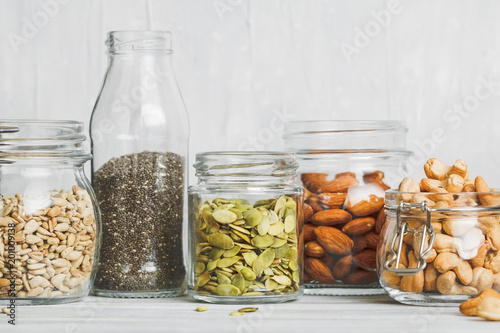 Fotomural Various nuts and seeds in glass jars over white wooden table against white background
