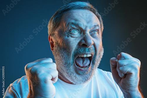 Obraz na płótnie The senior emotional angry man screaming on blue studio background