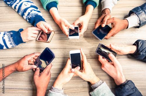 Hands circle using phones on table top view - Multiracial group of people holding mobile devices sitting around at office desk - Concept  of modern technology addiction