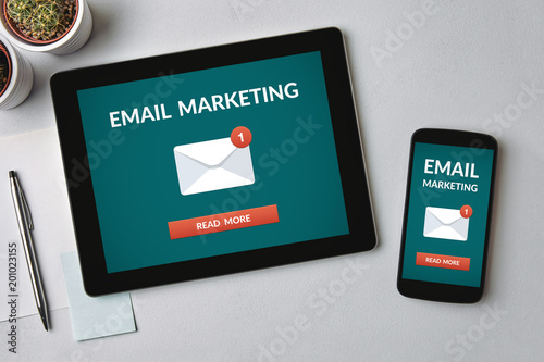 Email marketing concept on tablet and smartphone screen over gray table. All screen content is designed by me. Flat lay