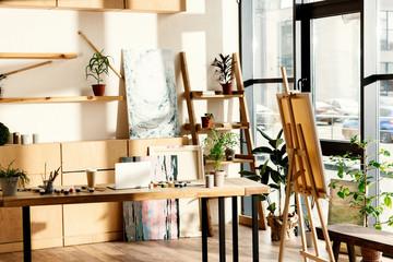interijer umjetničkog studija s slikarskim priborom i prijenosnim računalom na stolu