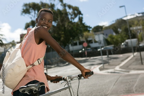 Woman walking with bicycle in city street