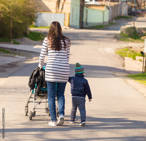 Fotografia, Obraz  A woman with a baby and a stroller walk along the road