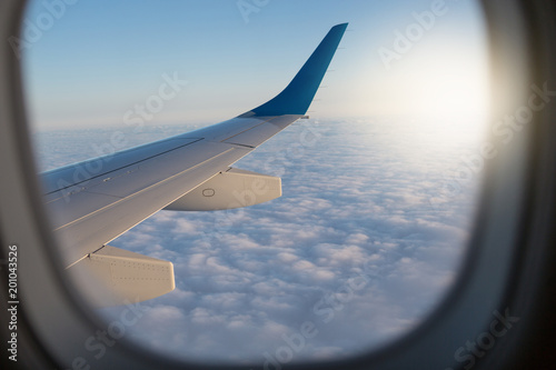 Fotografie, Obraz  view through the airplane window, window frame, above the clouds, visible part o