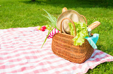 Picnic Backet Full Of Food And Drinks On Checkered Tablecloth
