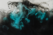 Close Up View Of Mixing Of Light Gray, Turquoise And Black Paints Splashes In Water Isolated On Gray