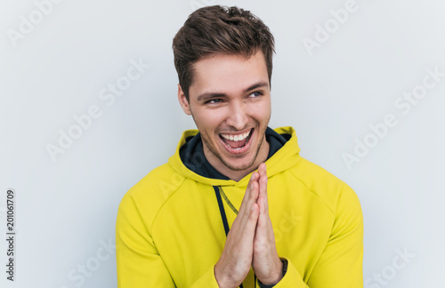 Studio closeup shot of sneaky sly and scheming young European man dressed in stylish yellow hoodie  looking at camera with mysterious smiles, male making gesture as if washing his hands Canvas Print