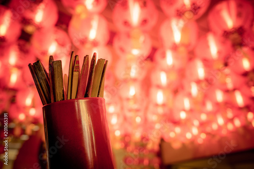 Photo  Close up of fortune sticks or Seam-Si or Chi-Chi sticks, shake for future fore with red Chinese paper lamp in the background