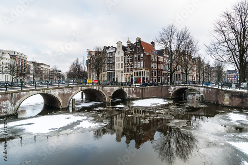 Stunning view of Amsterdam canal frozen with snow during the cold wave in February 2018 on a very cold winter day.