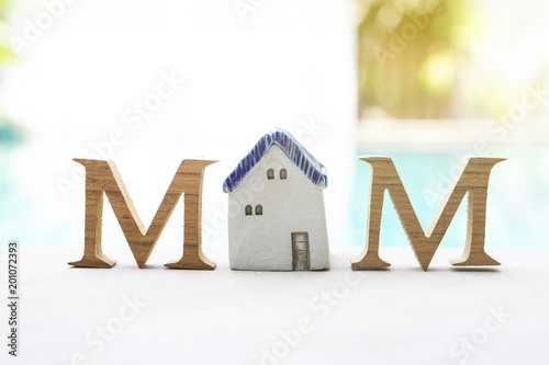 Mother's day concept, Wooden M text with vintage style ceramic house over blurred swimming pool background, outdoor day light