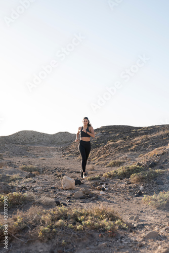 Young female runner running on dirt track in arid landscape, Las Palmas, Canary Islands, Spain