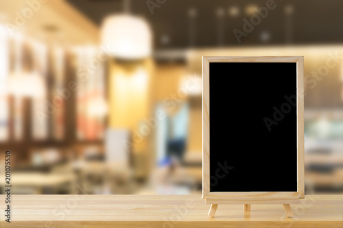 Fototapeta Blank chalkboard on wood table with copy space for your text message or product display in uxury restaurants in the mall blur background. obraz na płótnie