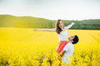 I feel free! Joyful young female raises hands being on man`s hands, pose together on yellow flower field during sunny summer weather. Romantic couple have fun outdoor. Relationships concept.