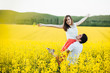 Portrait of happy young family couple feel happiness and freedom, pose together at yellow meadow against blue sky, demonstrates positiveness and true relationship. Romantic young people outdoor
