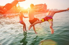 Group Of Happy People Having Fun Jumping In The Sea Water From A Pier. Friends In Mid Air On A Sunny Day Summer Pool Party. Vacation , Friendship , Youth Concept.