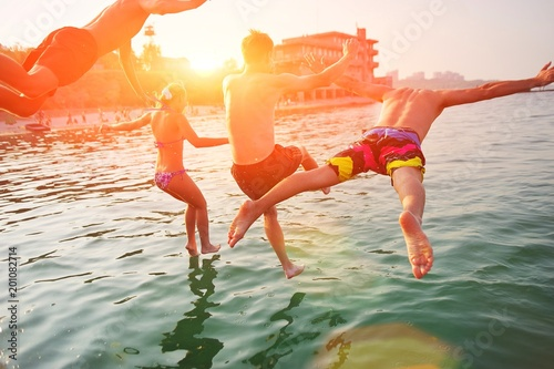 Poster  Group of happy people having fun jumping in the sea water from a pier